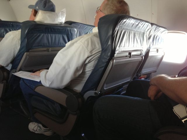 photo of three overweight middle aged men sitting in airplane first class