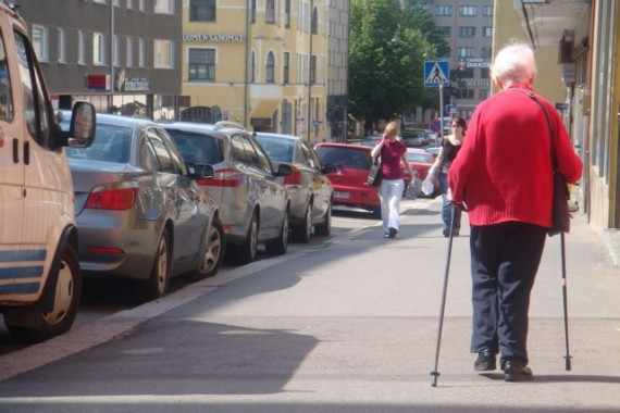 Elderly woman walking using cross country ski poles
