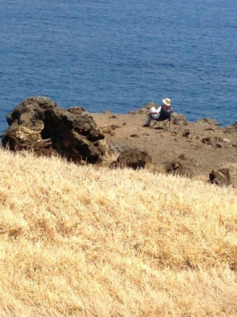 Person sitting at Hawaiian ocean front cliff view