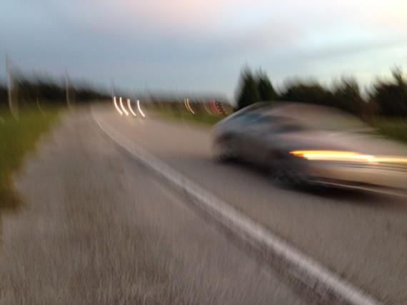 Blurry car passing runner along highway