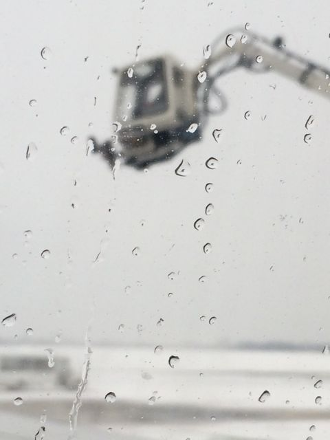 Looking out a Delta jet window at de-icing truck