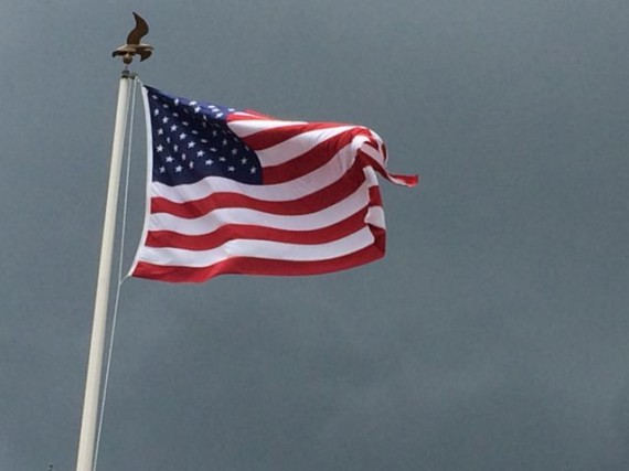 American Flag blowing in the wind against a dark sky