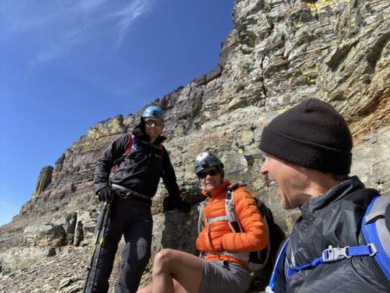 three hikers near mountain summit
