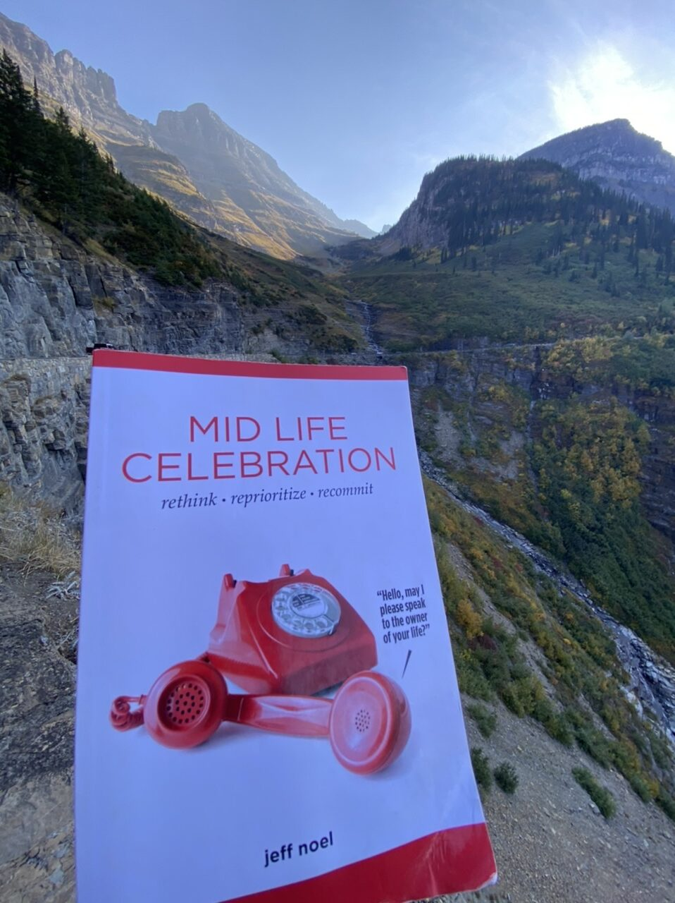Book entitled mid life celebration with mountains in the background