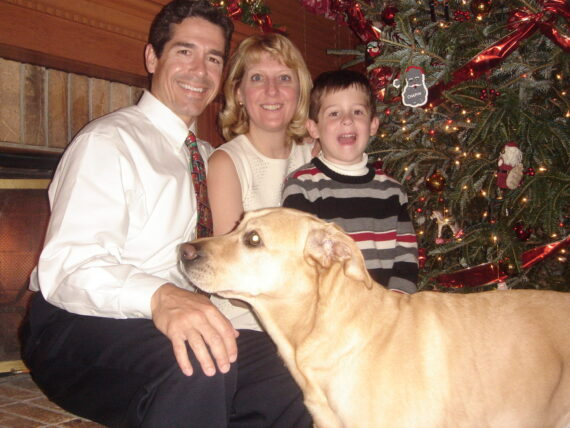 Family with dog next to Christmas tree