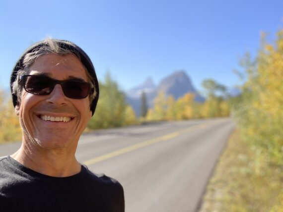 Man standing on road with mountains in the background