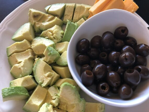 Plate with avocado, olives and cheese