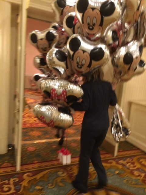 Person carrying lots of Mickey Mouse balloons