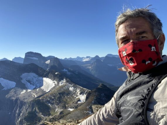 Face masked man with mountains in the background