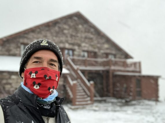 Man in a mask next to mountain  Chalet covered in snow