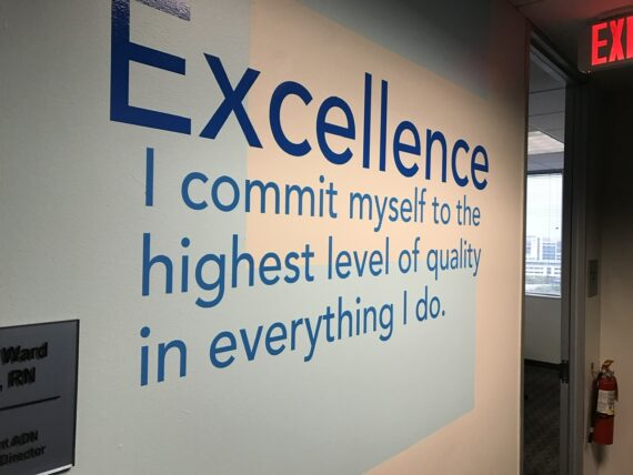 Quote about excellence on a corporate hallway wall