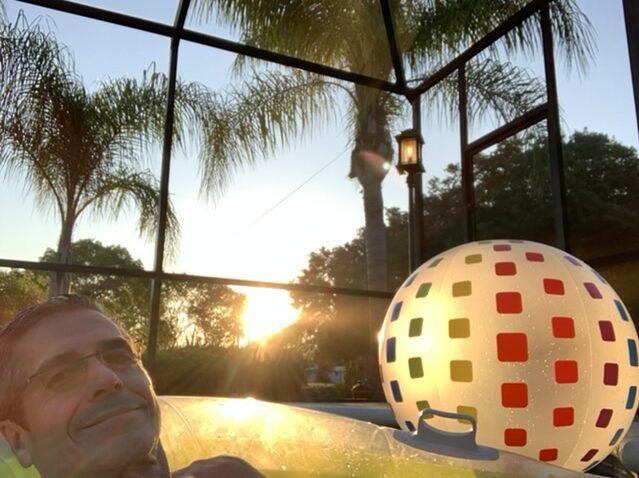 man in pool float as sun sets