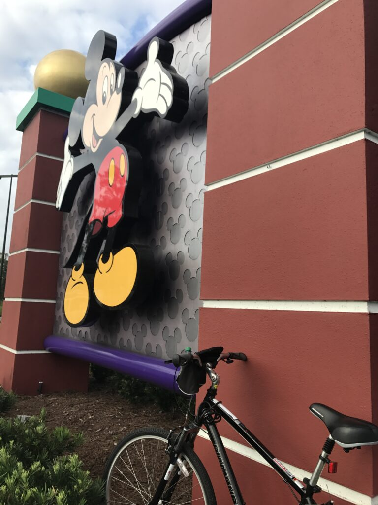 Bicycle park next to large Mickey Mouse welcome sign