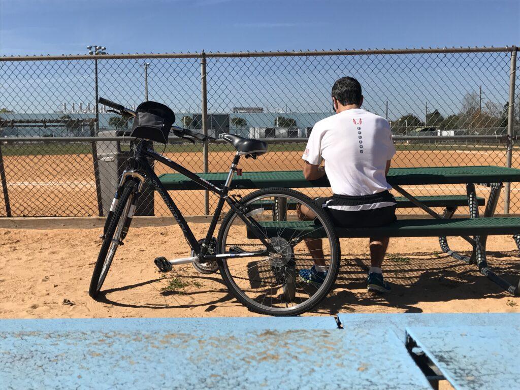 man sitting at picnic table at softball field