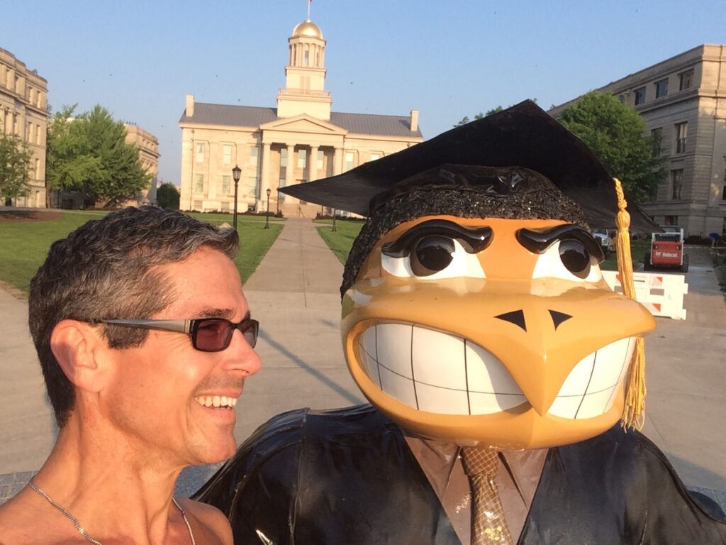 University of Iowa statue and shirtless man posing for camera